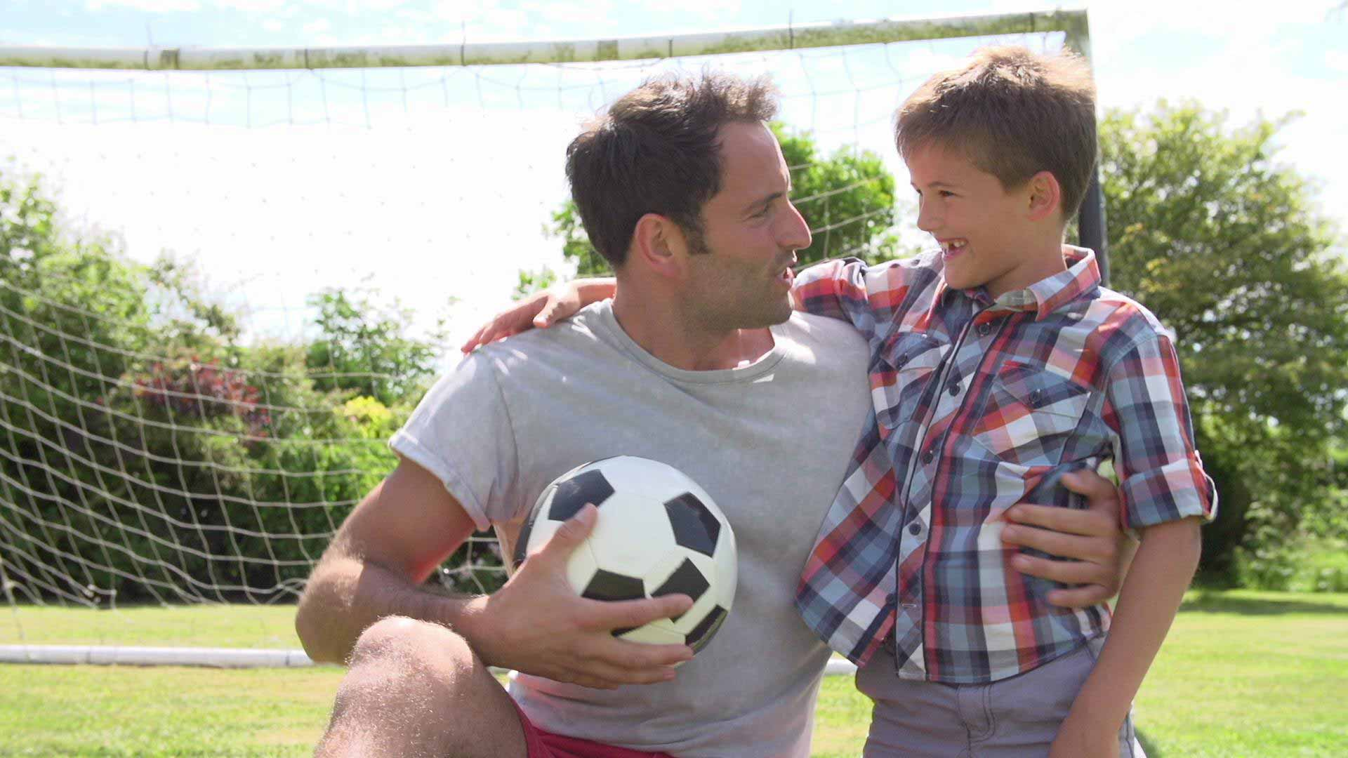 father teaching son soccer