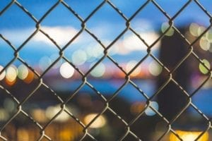 a chainlink fence and city lights